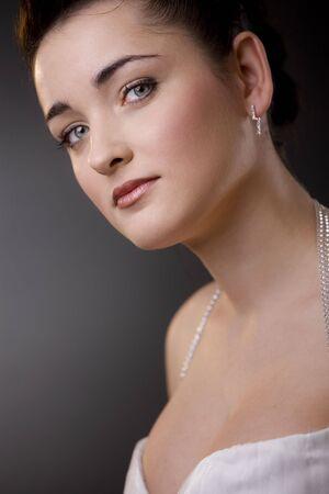 Closeup portrait of a beautiful bride wearing white wedding dress and makeup. photo