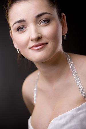 Closeup portrait of a beautiful bride wearing white wedding dress and makeup, smiling and looking at camera. photo