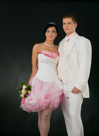 Portrait of wedding couple wearing white and pink. Bride holding bouquet of flowers, groom put an arm around her. photo