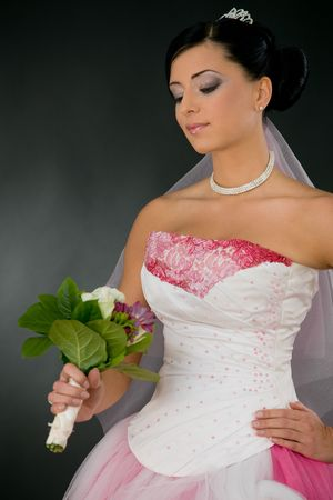 Beautiful young bride in white and pink wedding dress looking at bouquet of flowers, smiling. photo