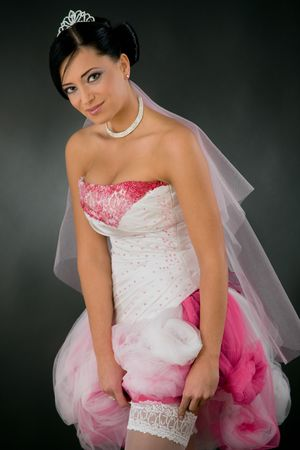Beautiful young bride in tied up, white and pink wedding dress adjusting her stockings, looking at camera, smiling. photo