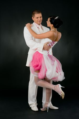 Weddling couple cuddling. Bride wearing tied up, pink and white wedding dress and stockings.