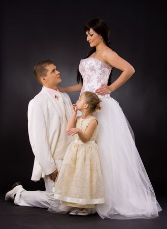 Portrait of wedding couple and little girl bridesmaid. Bride wearing romantic white wedding dress, groom kneealing if front of her. Stock Photo - 6508687