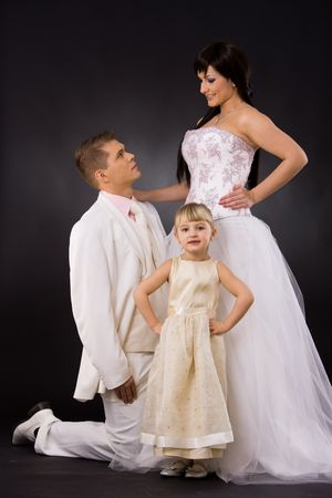 Portrait of wedding couple and little girl bridesmaid. Bride wearing romantic white wedding dress, groom kneealing if front of her. photo
