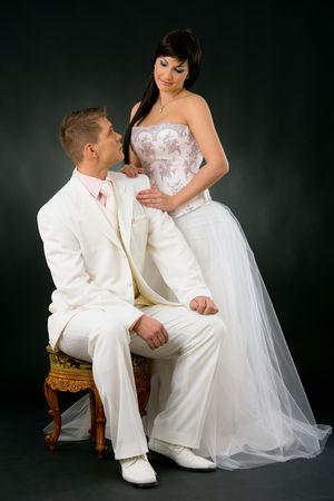 attire: Portrait of wedding couple. Bride wearing romantic white wedding dress, standing beside groom in white suit, sitting on chair. Looking at each other, smiling. Stock Photo