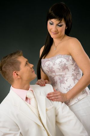 Portrait of wedding couple. Bride wearing romantic white wedding dress, leaning on groom in white suit. Looking at each other, smiling.