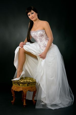 wedding photography: Beautiful bride showing her leg in white shoe. Stock Photo