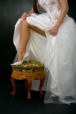 Closeup of brides leg in white, high heel shoe. photo
