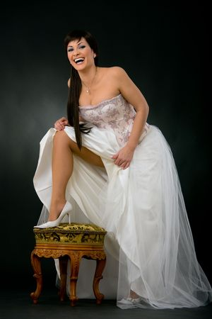 Sexy bride putting up her leg on chair, weaing white wedding dress and shoes. photo
