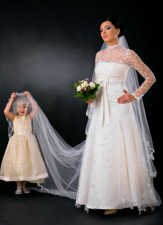 Bride posing in romantic white wedding dress, holding bouquet of flowers, little bridesmaid holding her veil. photo