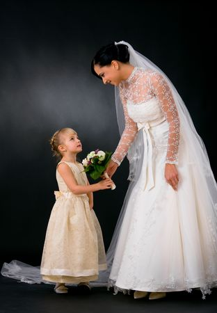 Bride wearing romantic white wedding dress giving bouquet of flowers to little bridesmaid, smiling. photo