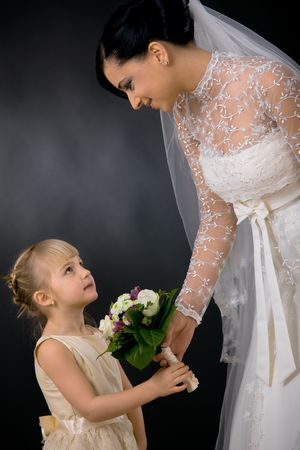 Bride wearing romantic white wedding dress with veil, giving bouquet of flowers to little bridesmaid, smiling. photo