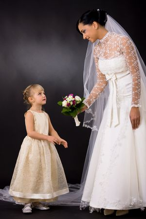 formal attire: Bride wearing romantic white wedding dress with veil, giving bouquet of flowers to little bridesmaid, smiling.