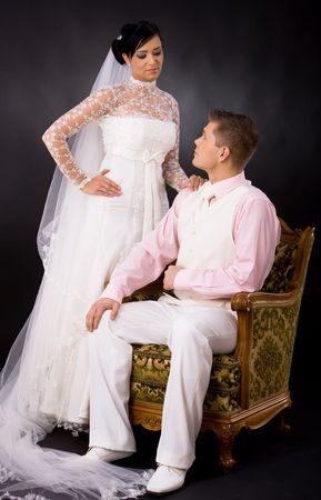 Studio portrait of wedding couple. Bride wearing romantic white wedding dress, groom sitting in arm chair, wearing white suit and pink shirt. Looking at each other. photo