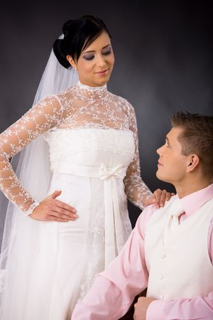 Studio portrait of wedding couple. Bride wearing romantic white wedding dress, groom in white suit and pink shirt. Looking at each other. photo