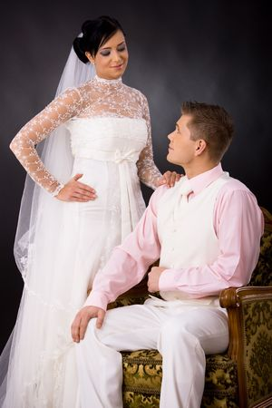 Studio portrait of wedding couple. Bride wearing romantic white wedding dress, groom sitting in armchair, wearing white suit and pink shirt. Looking at each other. photo