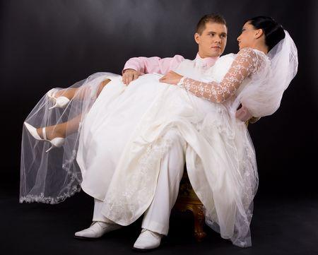 human photography: Retrato de estudio de la pareja de la boda. Novio sentado en la silla y la celebraci�n de su novia, que es que llevaba vestido de boda rom�ntica de blanco. Mirando mutuamente. Foto de archivo