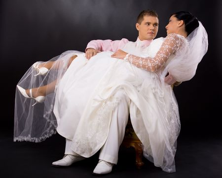 black and white photography: Studio portrait of wedding couple. Groom sitting on chair and holding his bride, who is wearing romantic white wedding dress. Looking at each other. Stock Photo