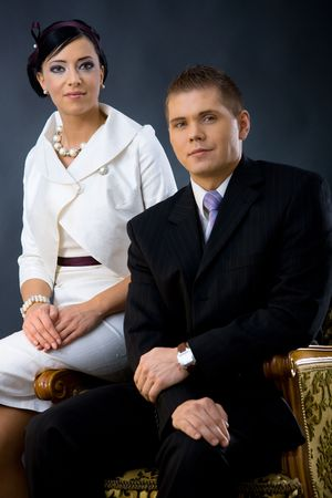 evening wear: Portrait of young couple dressed in elegant clothes, sitting on armchair. Woman wearing white cocktail shirt with jacket, man wearing three-pieces dark suit, looking at camera, smiling. Stock Photo