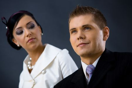 Closeup portrait of young couple dressed in elegant clothes. Woman wearing white dress, man wearing three-pieces dark suit. Selective focus placed on man. Stock Photo - 6508743