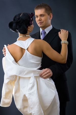 Young couple dressed in elegant clothes, cuddling, looking at each other. Woman wearing white dress, man wearing three-pieces dark suit. Stock Photo - 6508700