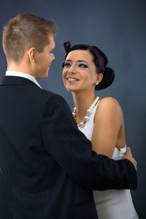 Portrait of young couple dressed in elegant clothes, looking at each other, smiling. Woman wearing white dress, man wearing three-pieces dark suit. photo