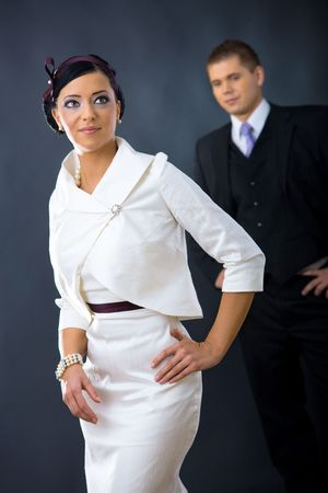 Portrait of young woman wearing white cocktail shirt with jacket, standing with hands on hip. Man in the background wearing three-pieces dark suit. photo
