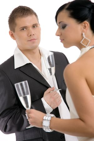 Trendy young coupledrinking champagne. Isolated on white background, selective focus on man. photo