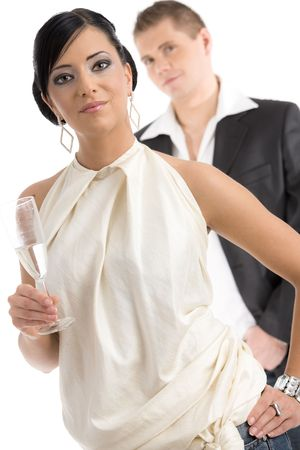 Young woman wearing white top holding a glass of champagne, smiling, her boyfriend in the background. Isolated on white. photo