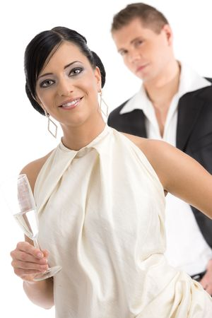 Happy young woman dressed for party holding a glass of champagne, smiling, her boyfriend in the background. Isolated on white. photo
