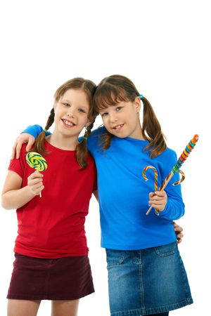 Portrait of smiling young girls hugging holding lollipops in hands. photo