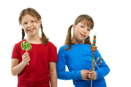 Elementary age girls smiling at camera holding lollipops in hands. photo