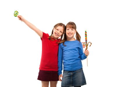 Smiling schoolgirls standing together holding lollipops, girl hugging other girl. photo