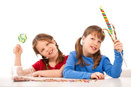 Laughing schoolgirls posing with sweets at table. photo
