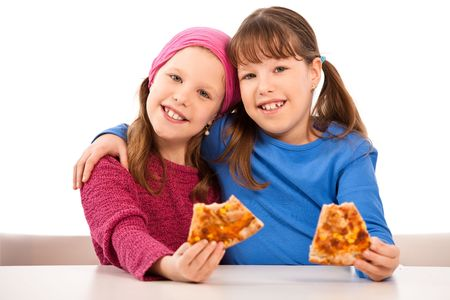 kids hugging: Girls smiling at table eating pizza slices.