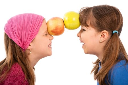 Laughing small girls facing each other, holding two apples together with forehead. photo