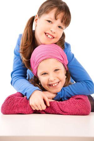 have: Portrait of smiling children, girl hugging other girl.