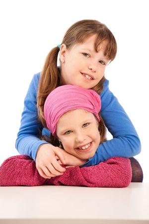 Portrait of smiling elementary age schoolgirls cuddling. photo