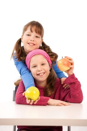 Portrait of smiling shcoolgirls holding apples out posing at table. photo