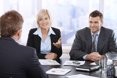 boardroom meeting: Confident businesspeople smiling at meeting table in office.