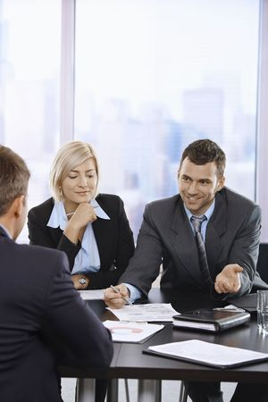 Smiling business people talking at meeting in office. photo
