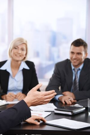 Hand in closeup at business meeting, coworkers listening in the background. Stock Photo - 6527217