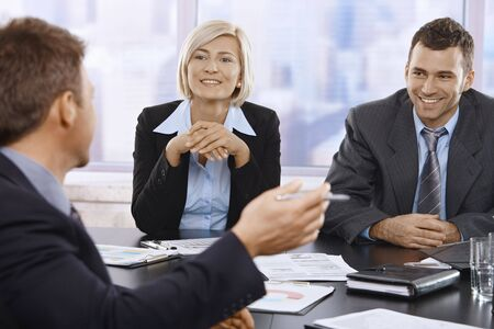 smilling: Smilling businesspeople at meeting table in office. Stock Photo