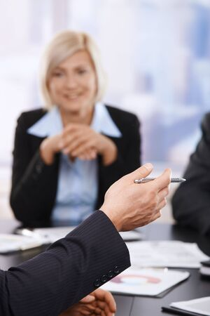 Hand in closeup holding pen at business meeting, partner listening in the background. photo