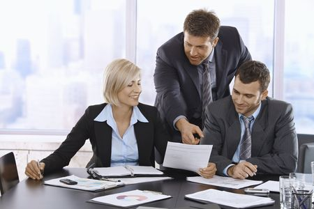 reviewing documents: Business people reviewing documents in office, businessman pointing at paper, smiling. Stock Photo