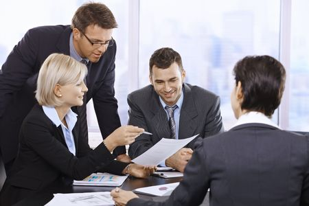Businesspeople working together at meeting table in office.