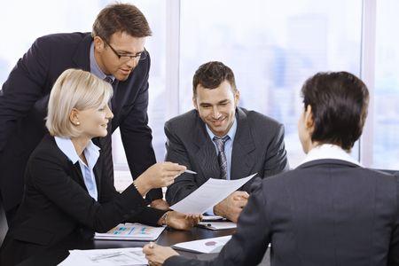 jornada de trabajo: Empresarios trabajando juntos en reuni�n de la mesa en el cargo.