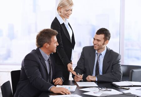 Businessman signing contract at meeting, smiling assistant pointing at document. photo
