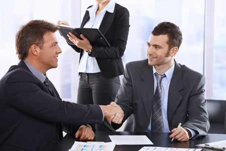 Businessmen shaking hands at meeting, sitting at table, assistant in background holding organiser. Stock Photo - 6527286
