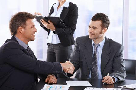 mani che si stringono: Imprenditori che stringe la mano a meeting, seduta al tavolo, assistente in sfondo azienda organizzatore.